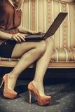 Фасонируйте женщину сидя на софе используя компьтер-книжку ПК Стоковое фото RF