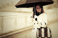Фасонируйте женщину с зонтиком идя в дождь на улице города Стоковое Изображение