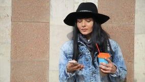 Фасонируйте красивую женщину latina испанца отправляя СМС на smartphone в кофе latte города выпивая акции видеоматериалы