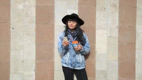 Фасонируйте красивую женщину latina испанца отправляя СМС на smartphone в кофе latte города выпивая видеоматериал