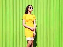 Фасонируйте красивую молодую женщину в желтых платье и солнечных очках Стоковое Изображение RF