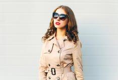 Фасонируйте красивый носить молодой женщины черные солнечные очки и пальто над серым цветом Стоковое Изображение