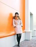 Фасонируйте милую женщину в пальто и шляпе представляя против красочное wal стоковое изображение