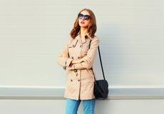 Фасонируйте милую модель женщины нося пальто и сумку над серым цветом Стоковое фото RF