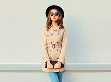 Фасонируйте милую модель женщины нося пальто и сумку черной шляпы представляя над серым цветом Стоковые Фотографии RF