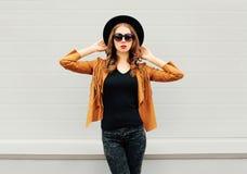 Фасонируйте милую модель женщины нося черную шляпу, солнечные очки, куртку над серым цветом Стоковые Изображения RF