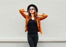 Фасонируйте милую модель женщины нося черную шляпу, солнечные очки, куртку представляя над серым цветом Стоковые Изображения RF