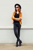 Фасонируйте модели молодой женщины нося солнечные очки черной шляпы над серым цветом Стоковое фото RF