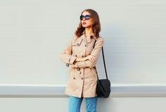 Фасонируйте модель женщины при пересеченные оружия нося сумку черноты пальто над серым цветом Стоковая Фотография