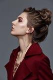 Фасонируйте модель стиля в бургундских аксессуарах пальто и искусства, представляя Стоковое фото RF