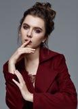 Фасонируйте модель стиля в бургундских аксессуарах пальто и искусства, представляя Стоковая Фотография RF