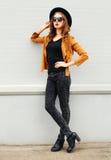 Фасонируйте модель элегантной женщины нося куртку солнечных очков черной шляпы представляя над серым цветом Стоковые Фото