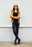 Фасонируйте модель элегантной женщины нося куртку солнечных очков представляя над серым цветом Стоковое Изображение