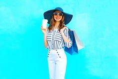 Фасонируйте довольно молодой усмехаясь женщине с носить кофейной чашки хозяйственные сумки, соломенную шляпу, белые брюки над кра стоковые изображения rf