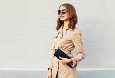 Фасонируйте довольно усмехаясь модель женщины нося пальто и черную муфту сумки над серым цветом Стоковое Изображение RF