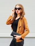 Фасонируйте портрету куртку солнечных очков милой молодой женщины нося и черную муфту сумки над серым цветом Стоковое Изображение
