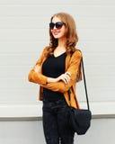 Фасонируйте портрету счастливую усмехаясь куртку солнечных очков женщины нося и черную муфту сумки над серым цветом Стоковое Изображение