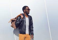 Фасонируйте портрету элегантный африканский носить человека солнечные очки и черная куртка утеса кожаная с сумкой в городе, копир стоковые фото