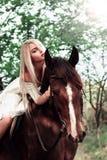 Фасонируйте портрет красивой белокурой девушки ехать лошадь в лесе в лете Стоковое Изображение