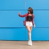 Фасонируйте портрет милой усмехаясь девушки битника в солнечных очках при smartphone и наушники делая selfie против Стоковые Фотографии RF