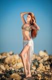 Фасонируйте портрет молодой сексуальной коричневой девушки в купальнике представляя на пляже Стоковые Фото