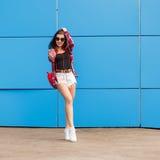 Фасонируйте портрет довольно усмехаться и женщину в солнечных очках с smartphone и наушниками против красочной голубой стены Стоковые Изображения RF