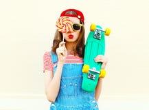 Фасонируйте портрет довольно холодной девушки с леденцом на палочке и скейтбордом над белизной Стоковое Изображение