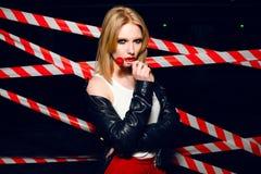 Фасонируйте портрет сексуальной белокурой девушки с конфетой в руке и красных губах на предпосылке предупреждающей ленты Стоковые Фото