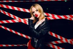 Фасонируйте портрет сексуальной белокурой девушки с конфетой в руке и красных губах на предпосылке предупреждающей ленты Стоковое Фото