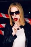 Фасонируйте портрет сексуальной белокурой девушки с конфетой в руке и красных губах на предпосылке предупреждающей ленты Стоковое Изображение