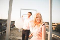 Фасонируйте симпатичных красивых пар представляя на крыше с предпосылкой города Молодой человек и чувственное белокурое внешнее l Стоковые Изображения RF