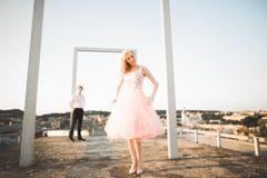 Фасонируйте симпатичных красивых пар представляя на крыше с предпосылкой города Молодой человек и чувственное белокурое внешнее l Стоковые Изображения