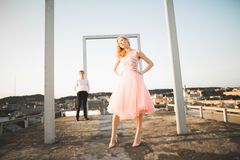 Фасонируйте симпатичных красивых пар представляя на крыше с предпосылкой города Молодой человек и чувственное белокурое внешнее l Стоковая Фотография