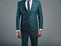 Фасонируйте стильную модель бизнесмена одетую в элегантном зеленом костюме представляя на сером цвете стоковая фотография
