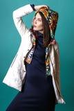 Фасонируйте съемку женщины в белом пальто, голубых drees в студии на зеленой предпосылке Стоковое Изображение RF