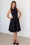 Фасонируйте съемку красивой сексуальной девушки в черном платье на предпосылке стены кирпича белой в студии Стоковые Фотографии RF