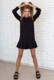 Фасонируйте съемку красивой сексуальной девушки в черном платье на предпосылке стены кирпича белой в студии Стоковые Изображения RF