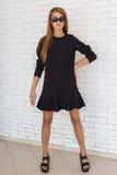 Фасонируйте съемку красивой сексуальной девушки в черном платье на предпосылке стены кирпича белой в студии Стоковые Изображения