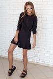 Фасонируйте съемку красивой сексуальной девушки в черном платье на предпосылке стены кирпича белой в студии Стоковое Изображение