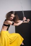 Фасонируйте фото красивой девушки представляя в студии Носящ желтые шорты, почерните ботинки Ремни над грудью держа цепь стоковое изображение rf