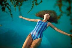 Фасонируйте фото привлекательной тонкой женщины с длинными светлыми волосами в элегантном striped купальнике тела ослабляя в басс Стоковое фото RF