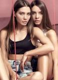 Фасонируйте фото привлекательных сестер близнецов кавказца представляя в pi Стоковое Фото