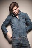 Фасонируйте человека смотря камеру пока исправляющ его джинсы Стоковое Фото