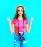 Фасонируйте шляпу лета соломы милой женщины нося, солнечные очки и винтажную камеру над красочной синью Стоковые Фото