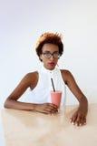 Фасонируйте smoothie молодой красивой африканской девушки выпивая отдыхая в кафе Стоковые Изображения RF