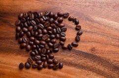 Фасоли чашки кофе на деревянной предпосылке Стоковая Фотография RF