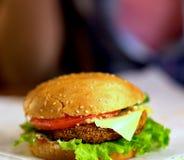 Фаст-фуд гамбургера с ветчиной на деревянной доске запачканная предпосылка Стоковые Фото
