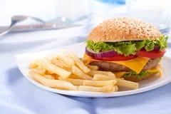 Фаст-фуд ест Фраи бургера и француза на плите Стоковое фото RF