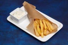 Фаст-фуд Зажаренные картошки на белой плите, голубой предпосылке Стоковые Изображения RF