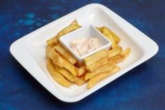 Фаст-фуд Зажаренные картошки на белой плите, голубой предпосылке Стоковые Изображения